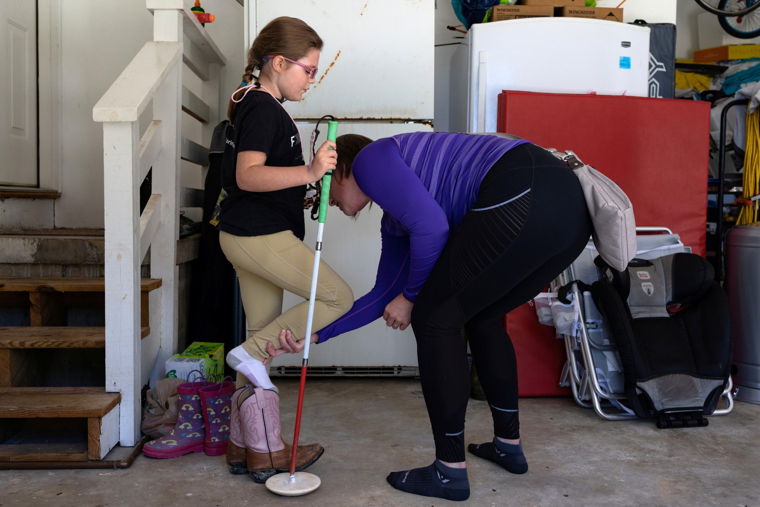 Anne Martha Corley helps her daughter, Ella Rose Corley, 8, who contracted an infection in early childhood that left her legally blind, put on her shoes in Vestavia Hills, Alabama, U.S., September 25, 2021. Picture taken September 25, 2021. REUTERS/Hannah Beier