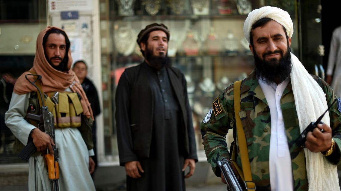 Taliban fighters stand guard on the backdrop of shops selling antiques and decorative merchandise at Chicken Street in Kabul on September 26, 2021. The once-bustling hotspot, where aid workers and adventurous tourists would shop for vintage tribal rugs, pottery and metalware, is almost empty of visitors looking for a bargain.