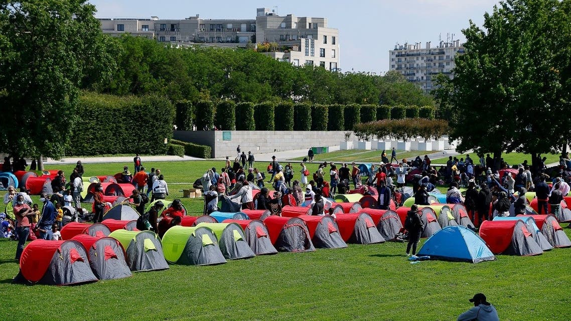 """Homeless people, including many migrants, set up a camp in the Andre-Citroen park, near the Ile-de-France region prefecture, on September 1, 2021, in Paris, as part of an action supported by associations' collective """"Collectif Requisition"""" to demand housing solutions. (AFP)"""