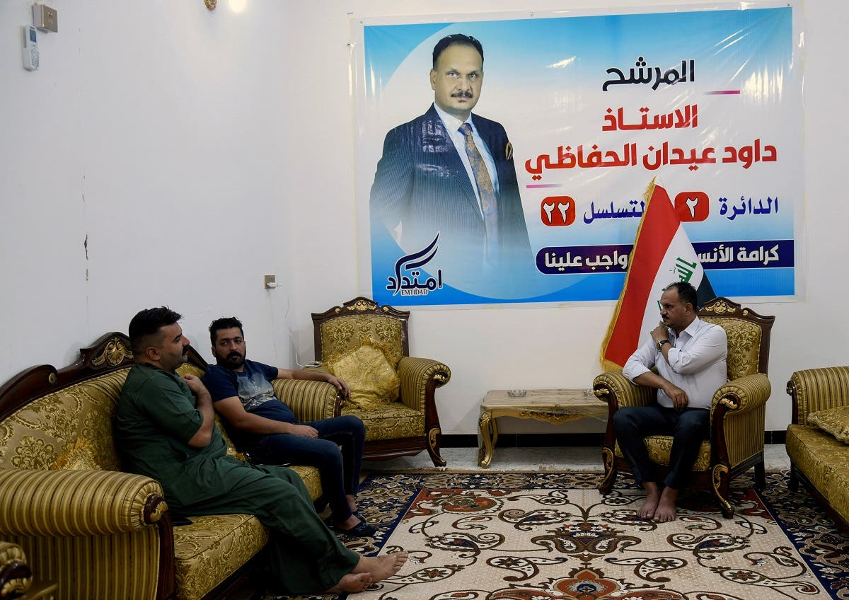 Dawood al-Hafathi, a candidate who participated in protests, sits with his supporters at his home in Nassiriya, Iraq, on September 23, 2021. (Reuters)