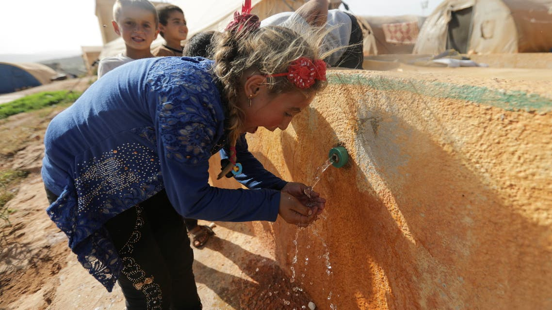 An internally displaced Syrian girl drinks water at Teh camp in northern Idlib, Syria May 5, 2021. Picture taken May 5, 2021. REUTERS/Khalil Ashawi