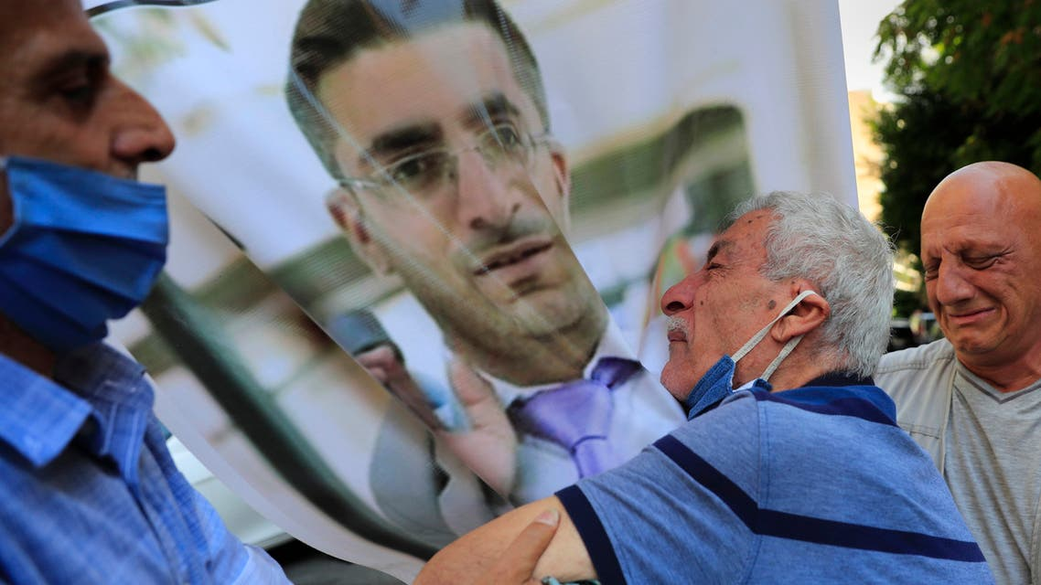 The father of Ibrahim Harb, 35, center, a Lebanese man who was critically injured in the massive explosion at Beirut's port last year and who died on Monday nearly 14 months after the blast, mourns on his son's portrait during his funeral procession, in Beirut, Lebanon, Tuesday, Sept. 28, 2021. (AP)