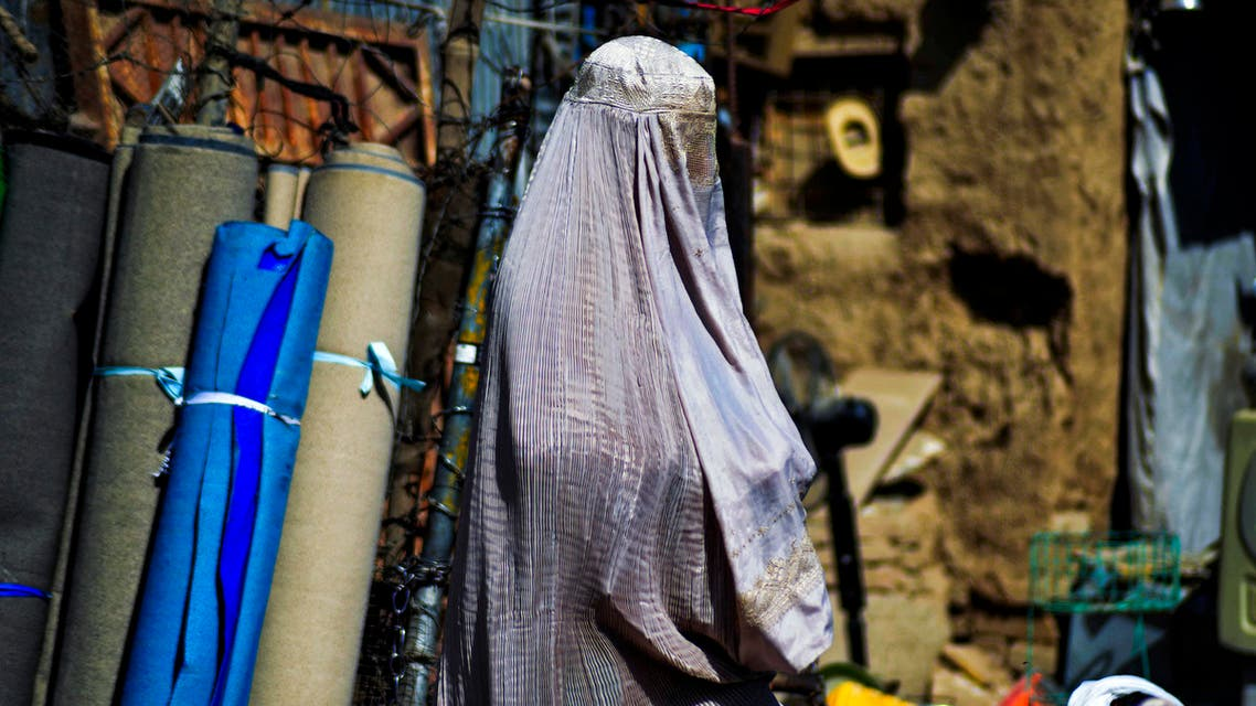 A burqa-clad woman walks past a stall selling secondhand items at a market in Kandahar on September 22, 2021.