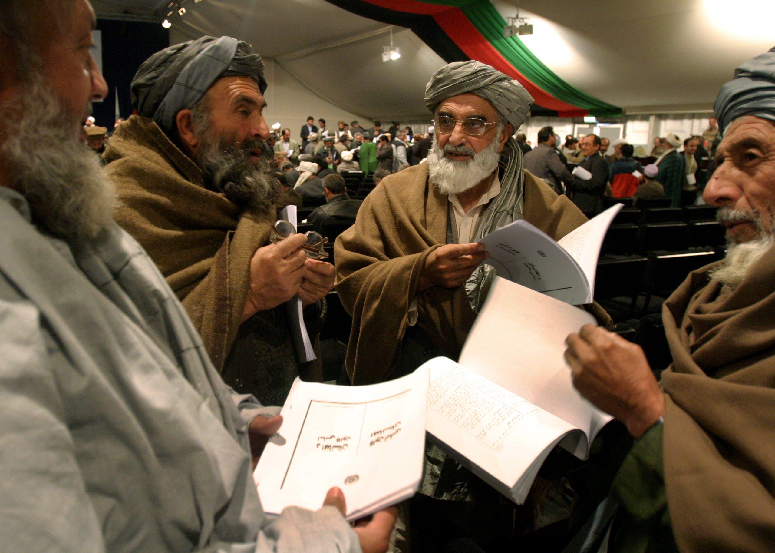أعضاء في البرلمان الأفغاني يقرؤون الدستور الجديد للبلاد الذي تم تبنيه في 2004