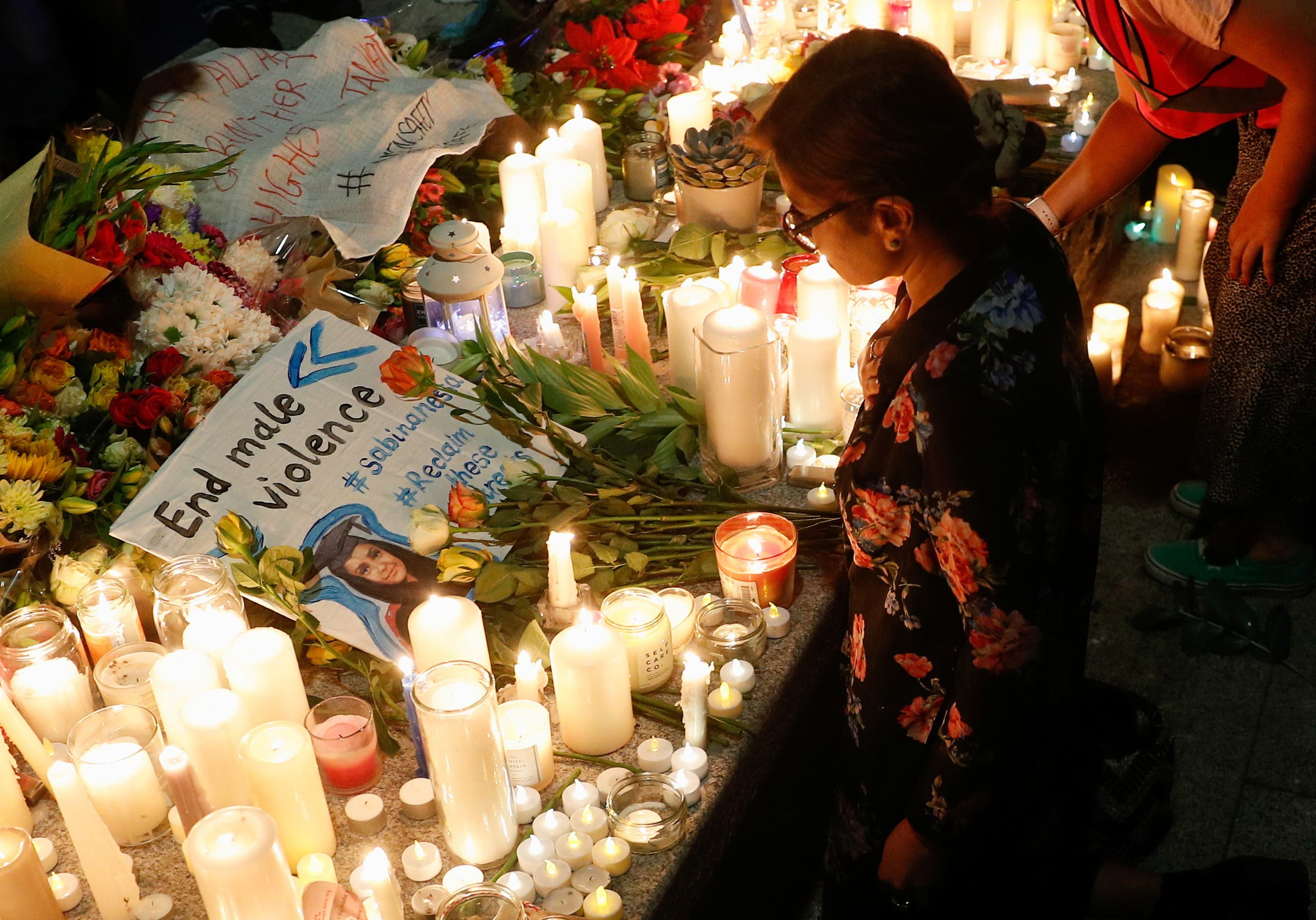 A placard is seen among flowers and candles during a vigil in memory of Sabina Nessa, a teacher who was murdered in Pegler Square, in London, Britain September 24, 2021. (Reuters)