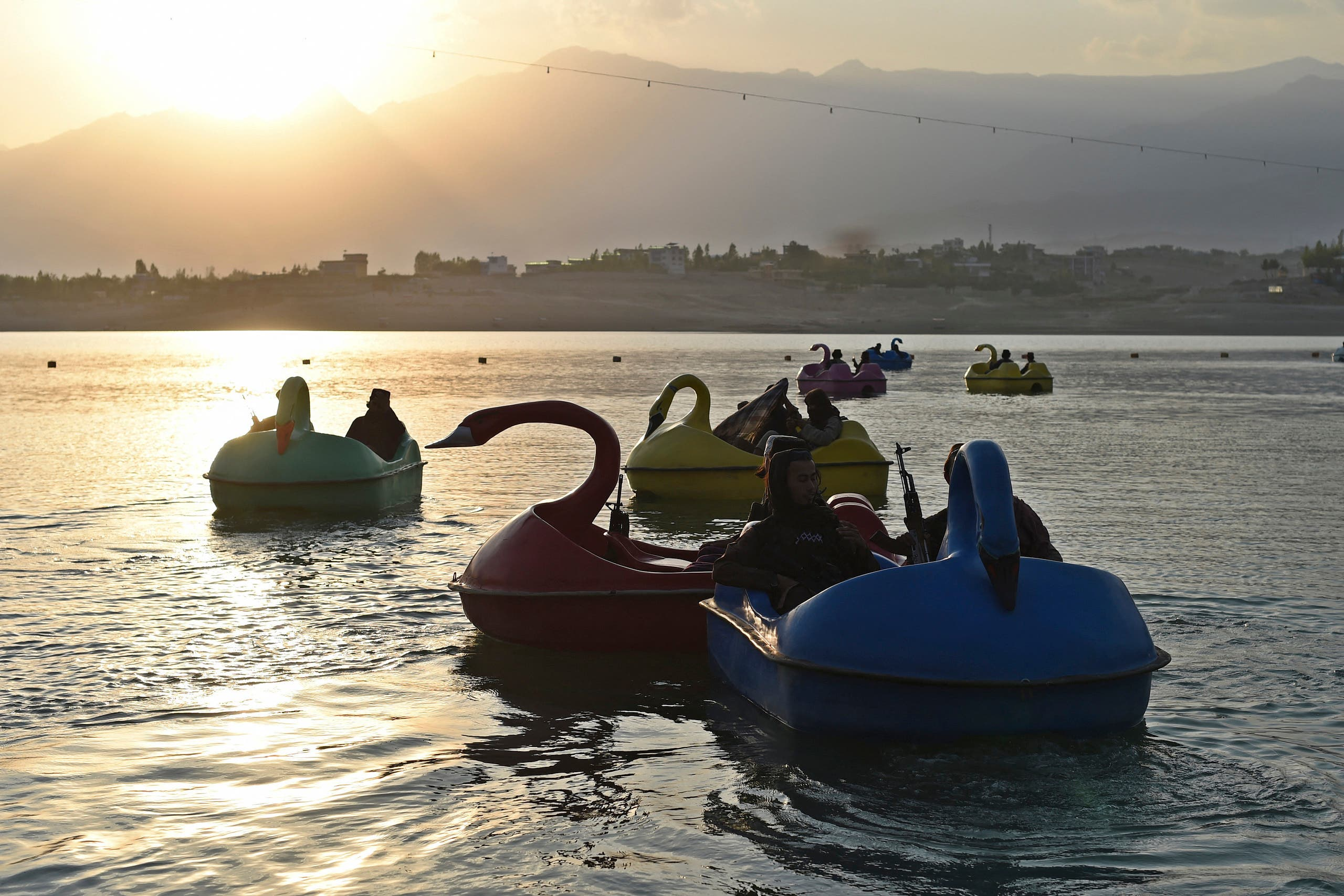 In this photograph taken on September 28, 2021 Taliban fighters ride on paddle boats at Qargha Lake on the outskirts of Kabul. (AFP)
