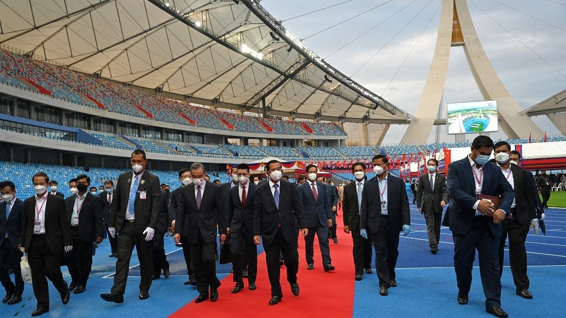 Cambodia's Prime Minister Hun Sen (centre R) and Chinese Foreign Minister Wang Yi (centre L) walk following a handover ceremony of the Morodok Techo National Stadium, funded by China's grant aid under its Belt and Road Initiative, in Phnom Penh on September 12, 2021. (AFP)