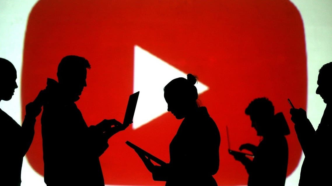 Silhouettes of laptop and mobile device users are seen next to a screen projection of the YouTube logo. (Reuters)