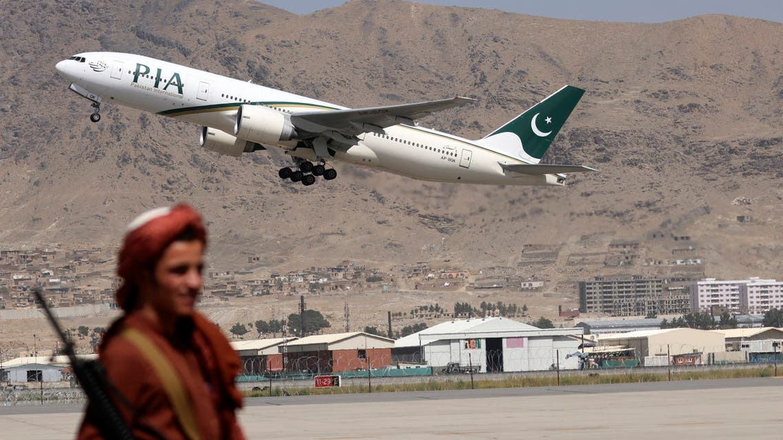 A Taliban fighter stands guard as a Pakistan International Airlines plane, the first commercial international flight to land since the Taliban retook power last month, takes off with passengers onboard at the airport in Kabul on September 13, 2021.