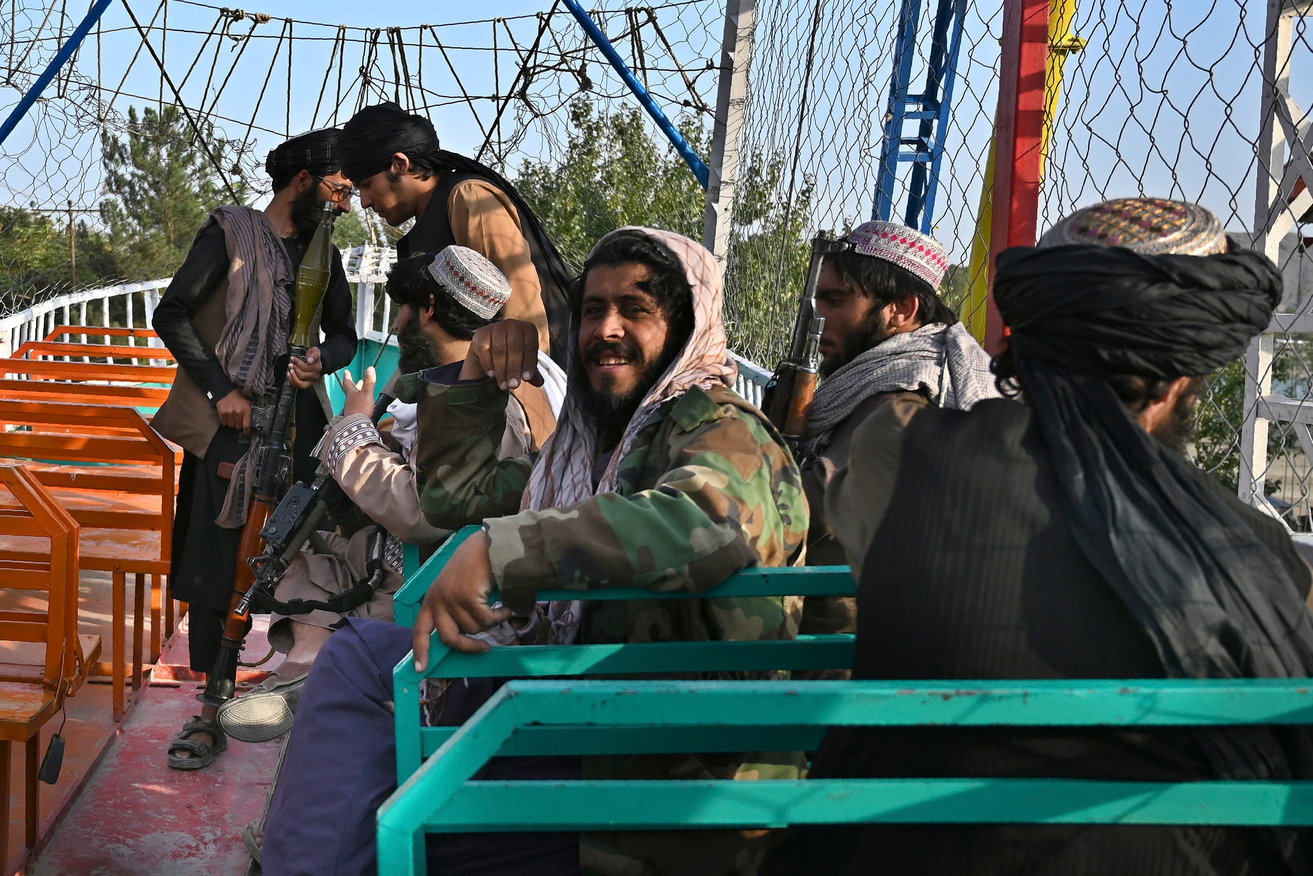 In this photograph taken on September 28, 2021 Taliban fighters enjoy a ride on a pirate ship attraction in a fairground at Qargha Lake on the outskirts of Kabul. (AFP)