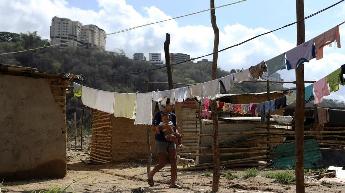 A woman walks across hanged clothes on a vacant lot where families are settling since they cannot afford to pay rent anymore, in the municipality of Sucre, near Caracas, Venezuela, on June 12, 2020. (Reuters)