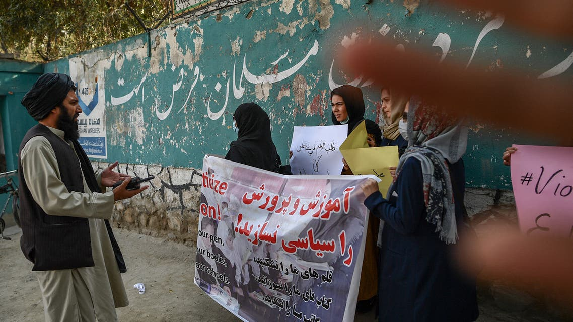 A member of the Taliban speaks with women protestors as another tries to block the view of the camera with his hand during a demonstration held outside a school in Kabul on September 30, 2021. (AFP)