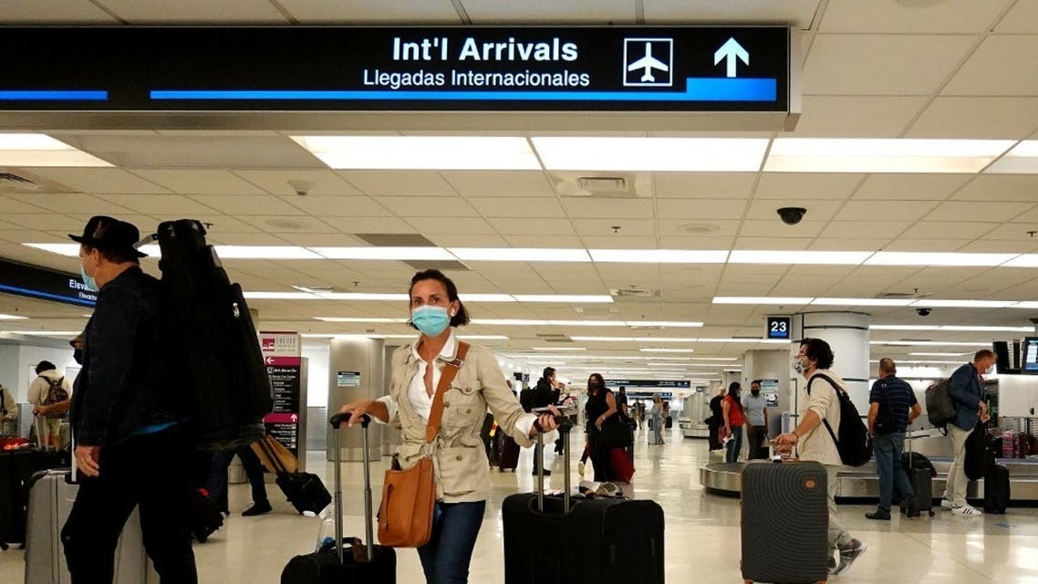 Travelers gather their luggage as they arrive at Miami International Airport on September 20, 2021 in Miami, Florida. (AFP)