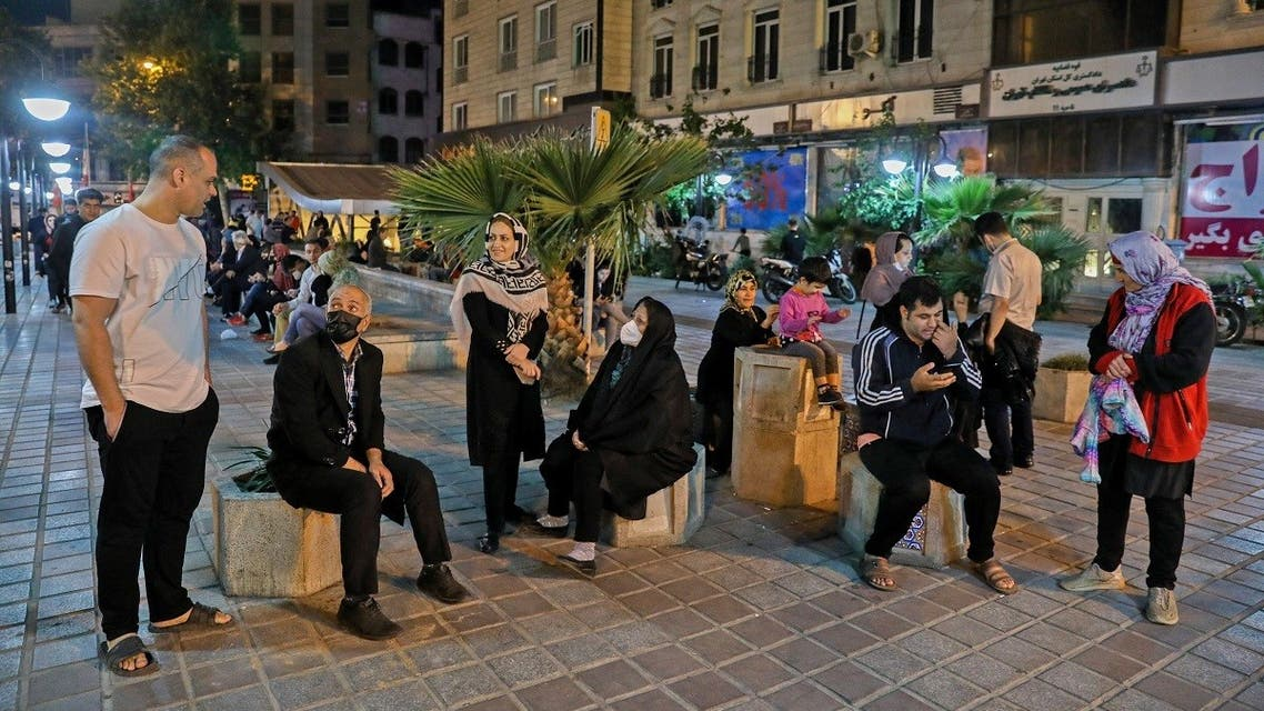 A file photo shows Iranians wearing masks against the coronavirus gather outside their buildings after an earthquake was felt in the capital Tehran on May 7, 2020. (Amir Kholousi/ISNA News Agency/AFP)