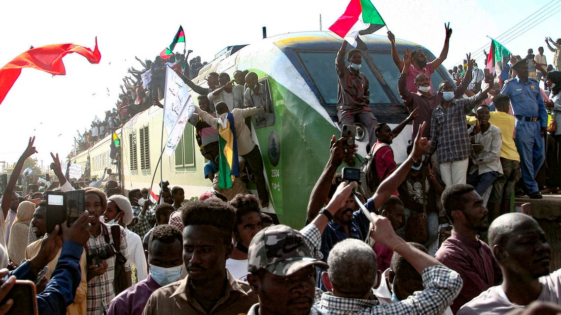 Sudanese protesters cheer as they greet fellow demonstrators upon their arrival on a train from Madani, the capital of Sudan's east-central al-Jazirah state, to join a rally in support of a civilian-led transition to democracy, on September 30, 2021. (AFP)