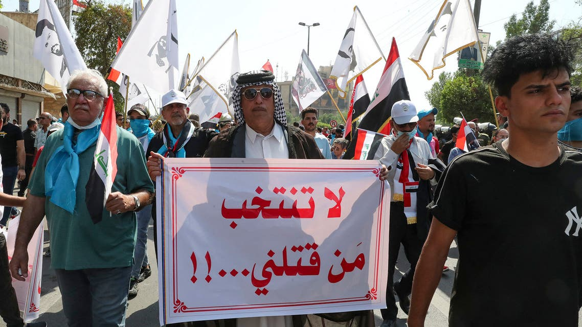 Iraqis hold placards as they rally at Fardous square in central Baghdad, on October 1, 2021, demanding justice for demonstrators killed during the October 2020 anti-government protests, ahead of the October 10 parliamentary elections. The writing in Arabic reads:  Don't vote for those who killed us. (AFP)