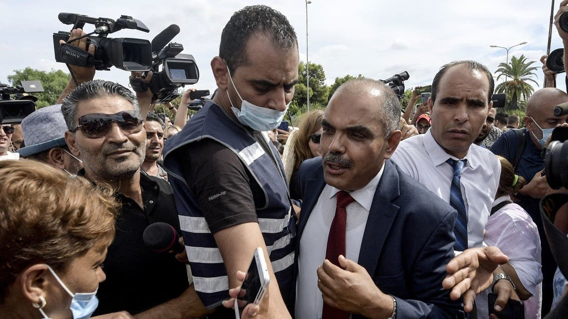 Journalists and members of the security forces surround Mohamed Goumani, a Tunisian deputy and member of the Annahda party, after being attacked by citizens in front of the Assembly headquarters, during a rally in the capital Tunis on October 1, 2021. (Fethi Belaid/AFP)