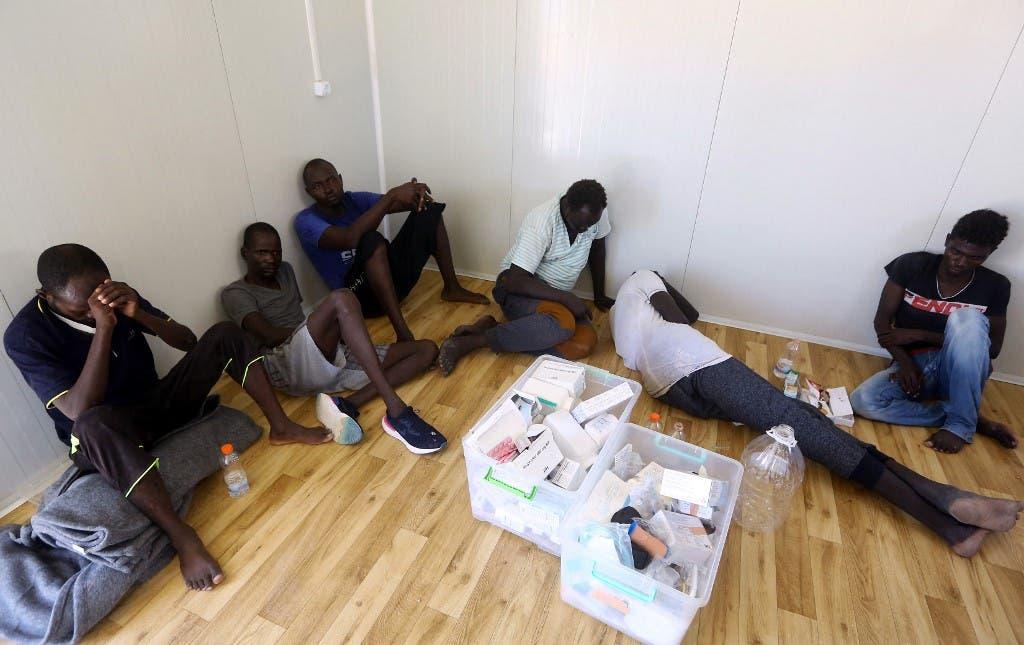 مهاجرون يجلسون على الأرض في مركز احتجاز في تاجوراء الليبية
