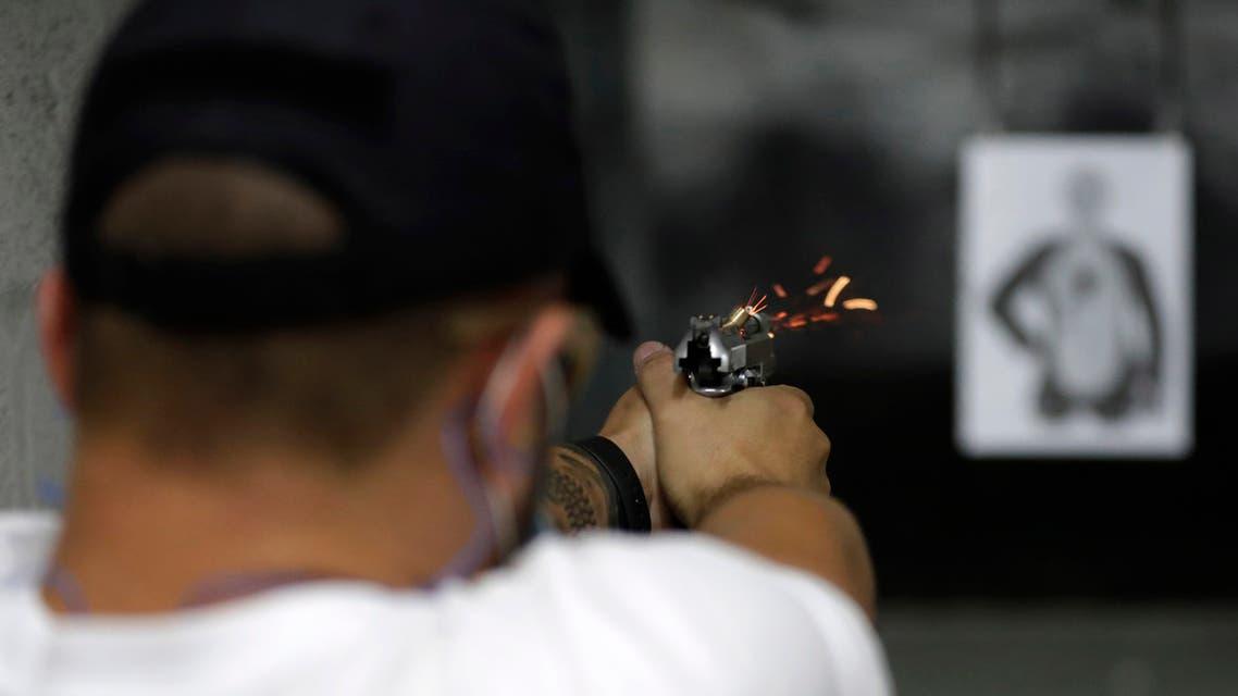 Rodrigo Amaral shoots at a target in the Valparaiso Shooting Club, on the outskirts of Brasilia, Brazil, Thursday, March 4, 2021. (AP Photo/Eraldo Peres)