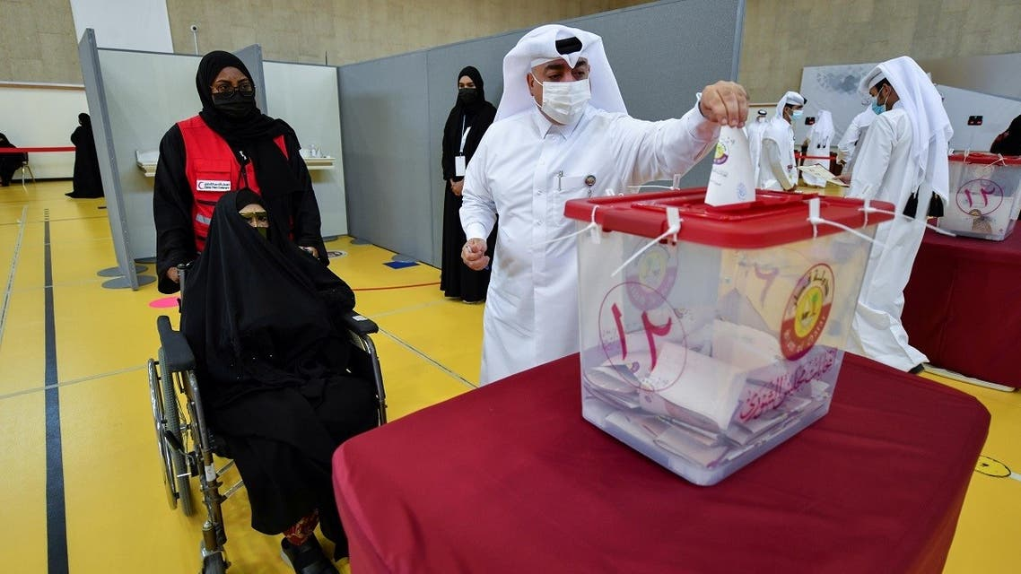 A man casts a ballot as a woman in a wheelchair looks on during the Gulf Arab state's first legislative elections for two-thirds of the advisory Shura Council, in Doha, Qatar October 2, 2021. (Reuters)