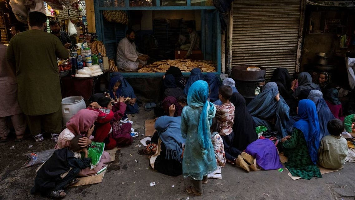 Afghan women and children sit in front of a bakery waiting for bread donations in Kabul's Old City, Afghanistan, Thursday, Sept. 16, 2021. (AP)