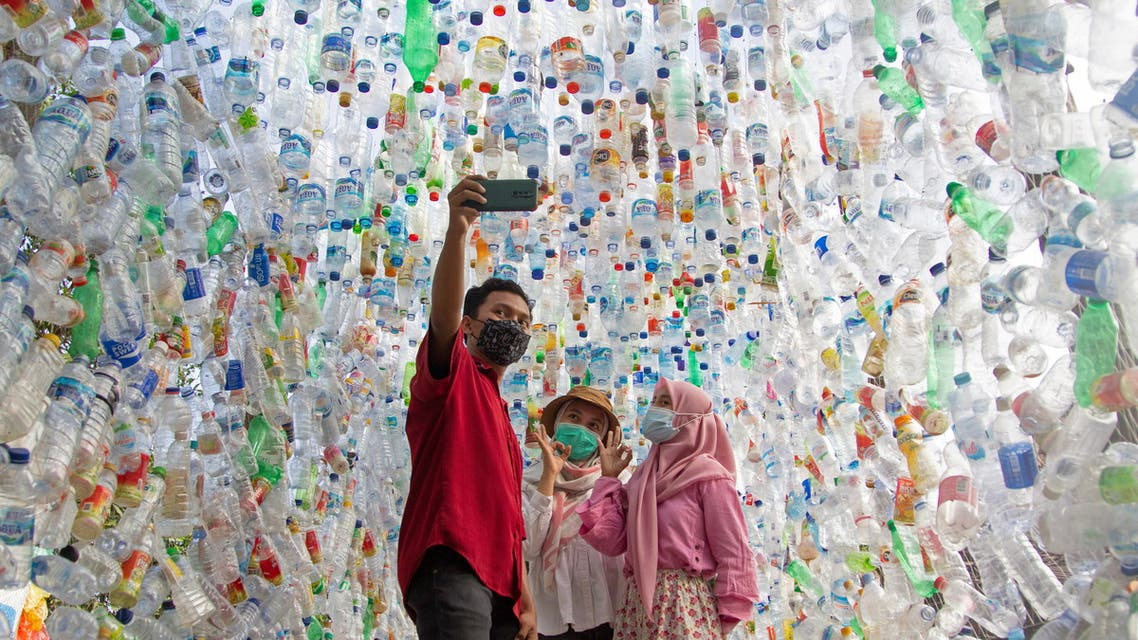 An Indonesian activist from ECOTON (ecological observation and wetland conservation) prepares an installation made with used plastic, including 4,444 bottles, collected from the river in Gresik on September 17, 2021, to raise public awareness of plastic waste in rivers and oceans.