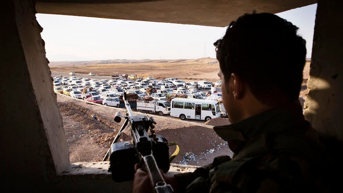 An Iraqi security forces member with his weapon takes position as people, who fled from the violence in Mosul, arrive at a camp for internally displaced people on the outskirts of Erbil. (Reuters)