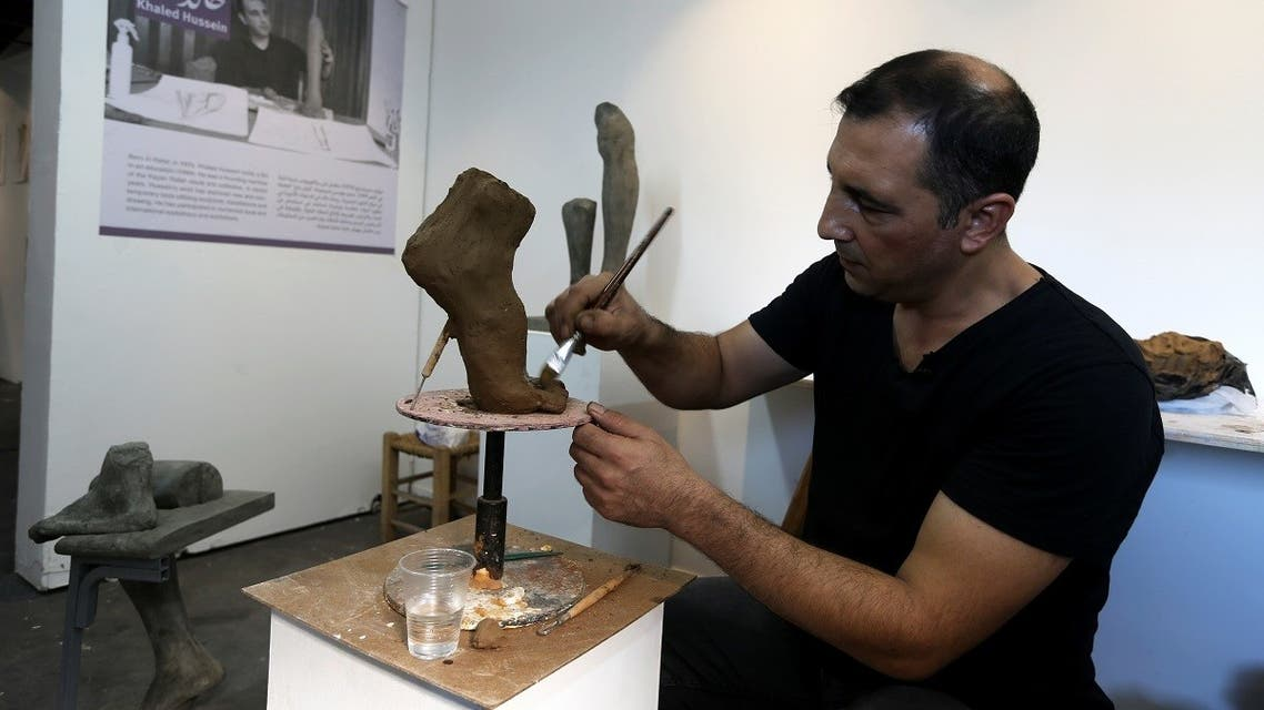 Palestinian artist Khaled Hussein works on a sculpture resembling an amputated foot in his workshop to bring attention to the plight of amputees in Gaza City, September 28, 2021. (Reuters/Ibraheem Abu Mustafa)