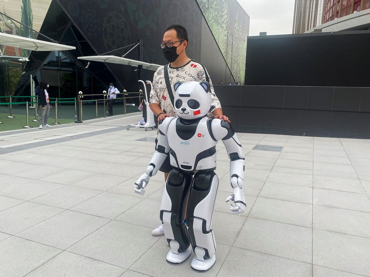 A man stands next to a panda robot at the Chinese Pavilion at the Expo 2020 in Dubai, UAE, on October 4, 2021. (Reuters)
