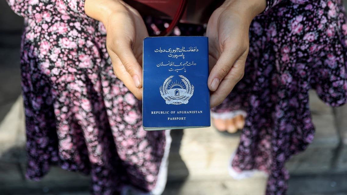 An Afghan refugee holds her passport in front of the German Embassy in a bid to acquire refugee visas from the European country, in Tehran, Iran September 1, 2021. (Reuters)