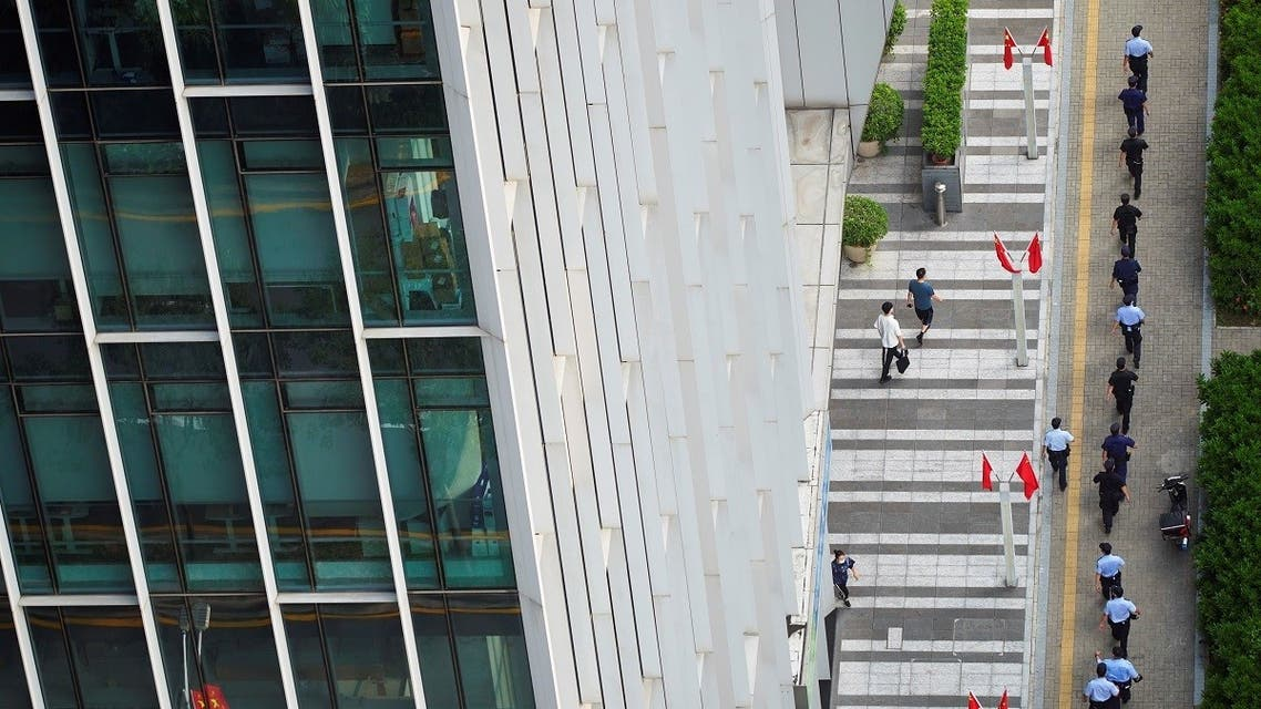 Police officers and security personnel walk outside the headquarters of China Evergrande Group in Shenzhen, Guangdong province, China, on September 30, 2021. (Reuters)