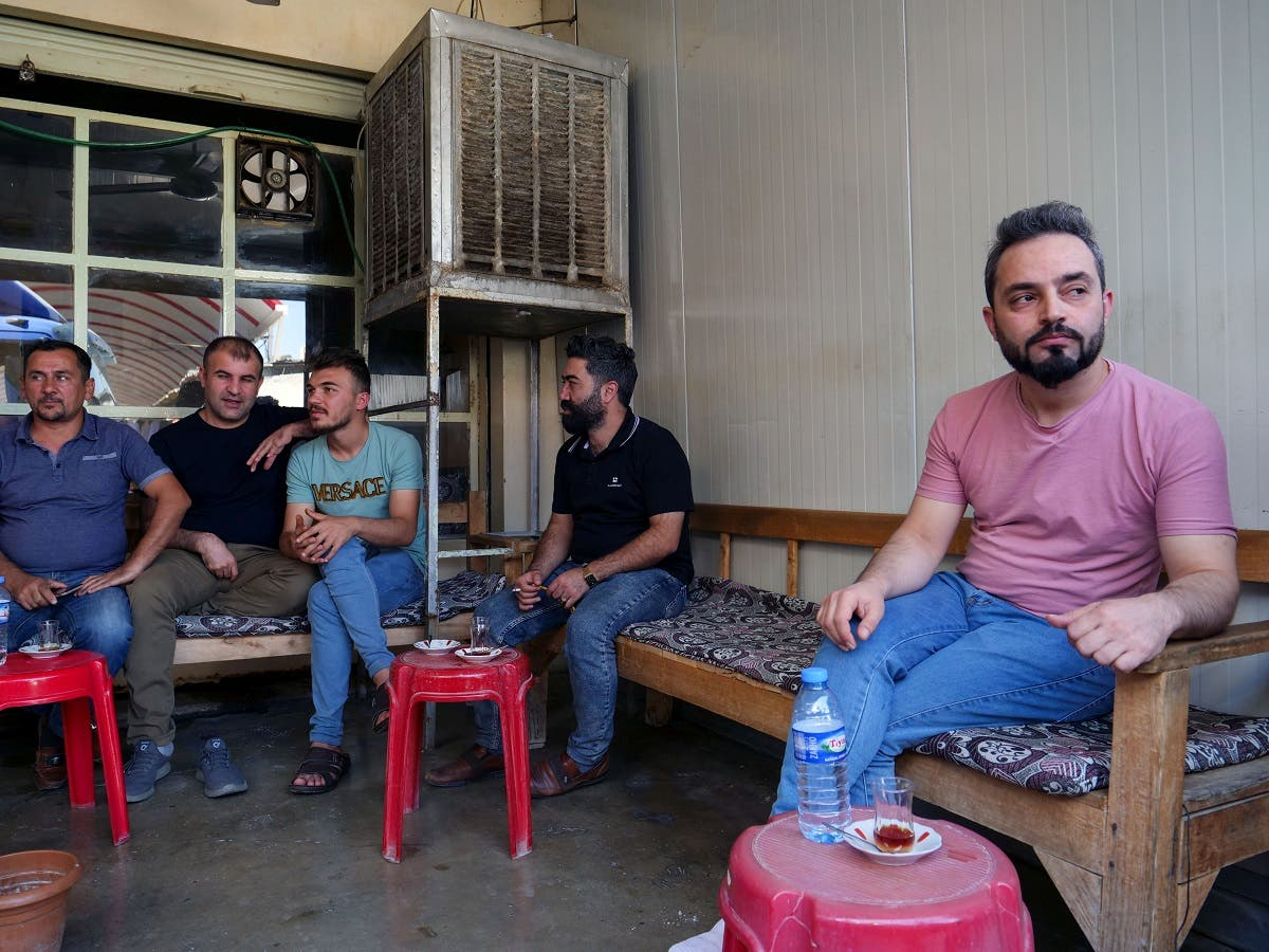 Abdullah Omar, a barber who has many relatives and friends who left to Belarus sits in a local tea shop in the town of Shiladze, Iraq September 22, 2021. (Reuters)