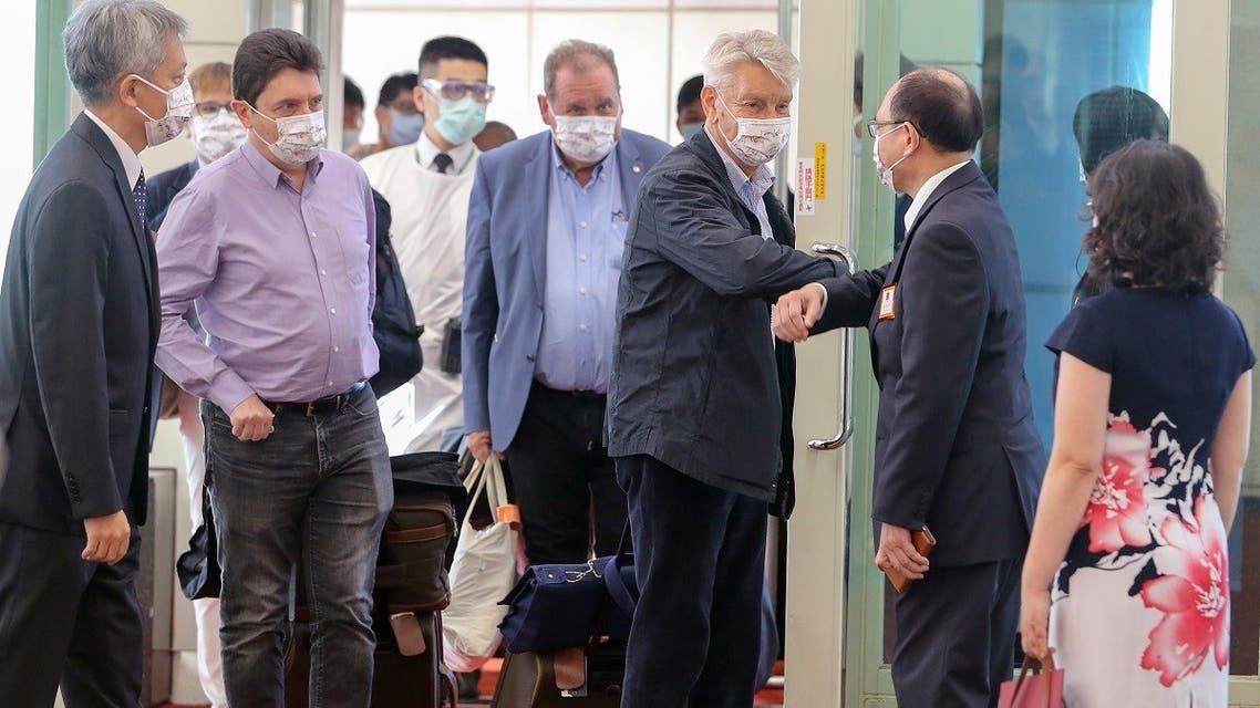French senator Alain Richard bumps elbows with a Taiwanese official upon arrival at the Taoyuan International Airport in Taiwan on Oct. 6, 2021.  (AP)