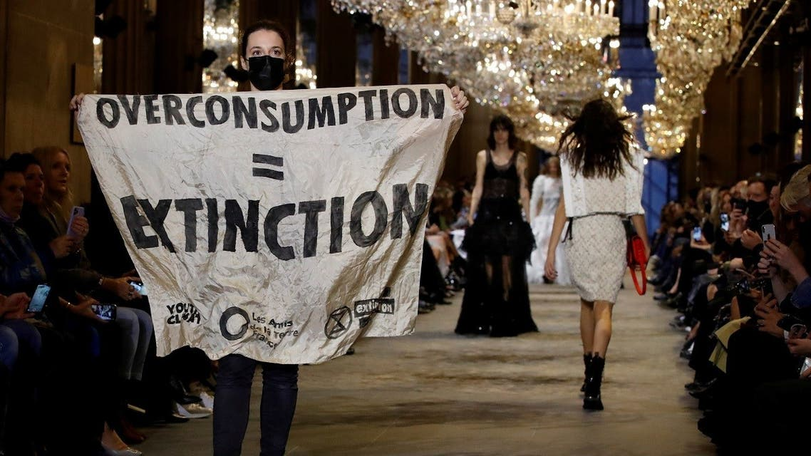"""An activist walks on the ramp with a banner that says """"Overconsumption = Extinction"""" as she crashes the designer Nicolas Ghesquiere Spring/Summer 2022 women's ready-to-wear collection show for fashion house Louis Vuitton during Paris Fashion Week in Paris, France, on October 5, 2021. (Reuters)"""