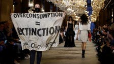 Protester with climate change banner crashes Louis Vuitton show, tackled by security