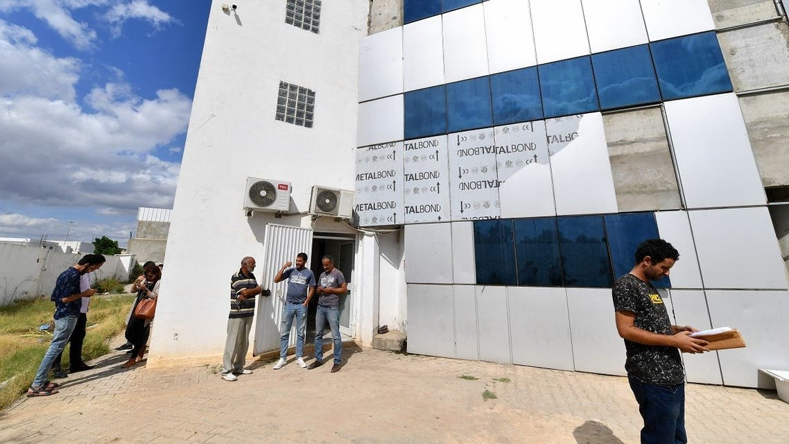 Employees gather outside the building housing the Zitouna TV channel on October 6, 2021, in the district of Mghira of greater Tunis, the country's capital. (Fethi Belaid/AFP)