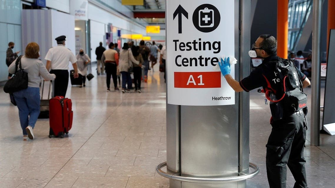 A worker sanitises a sign at the International arrivals area of Terminal 5 in London's Heathrow Airport, Britain. (Reuters)