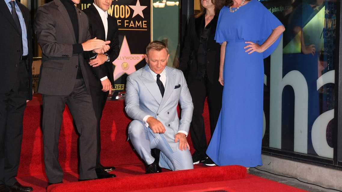 British actor Daniel Craig (C) kneels to look at his newly unveiled star, flanked by (from R) Chamber of Commerce Chair Nicole Mihalka, US producer Barbara Broccoli, US actor Rami Malek, Los Angeles City Councilmember Mitch O'Farrell and US screenwriter Michael G. Wilson during the ceremony to honor him with a star on the Hollywood Walk of Fame in Los Angeles, California, on October 6, 2021. (AFP)