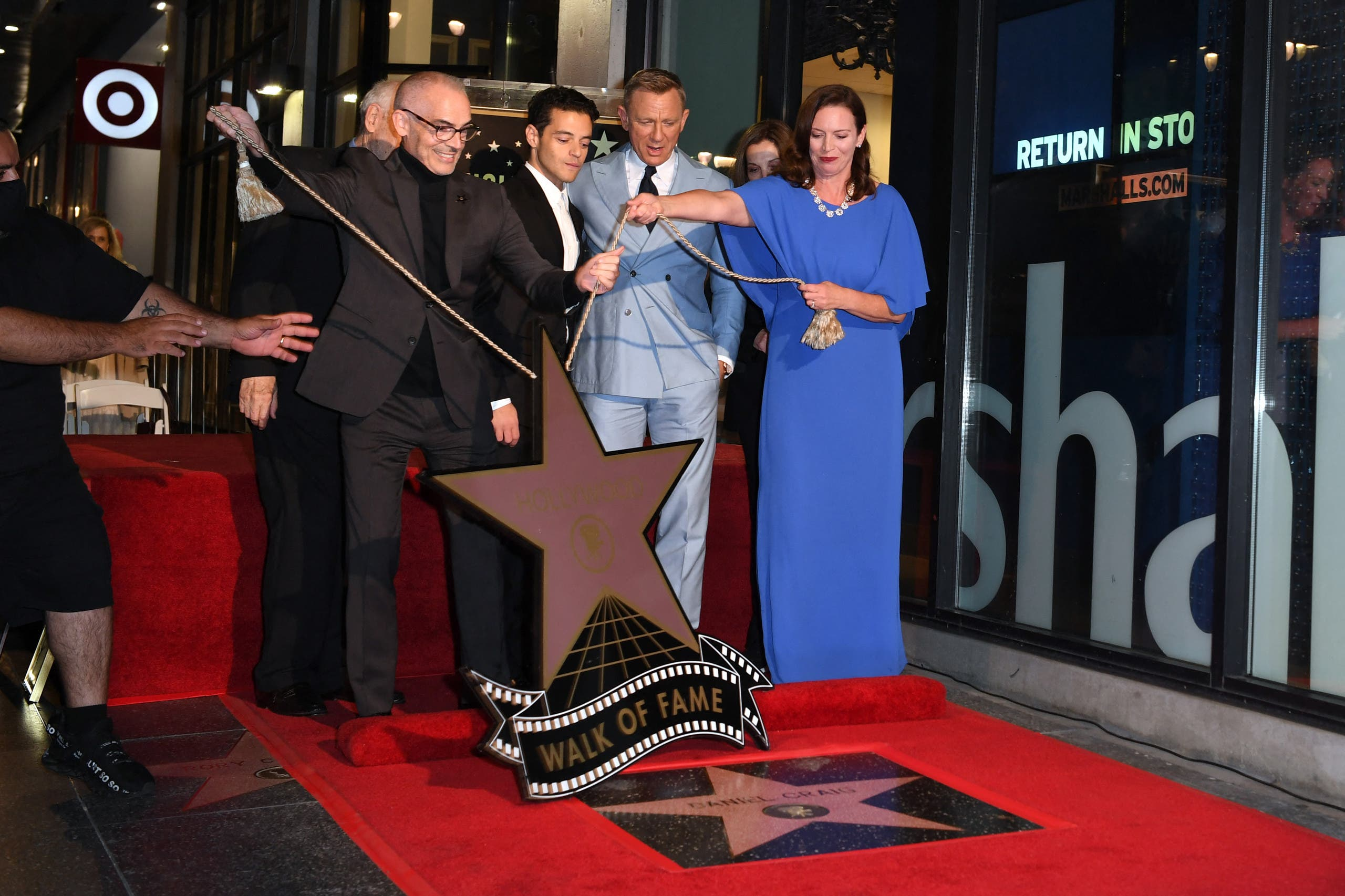 British actor Daniel Craig (2nd R), reacts as his star is unveiled, flanked by Chamber of Commerce Chair Nicole Mihalka (R), US actor Rami Malek (3rd R) and Los Angeles City Councilmember Mitch O'Farrell during the ceremony to honor him with a star on the Hollywood Walk of Fame in Los Angeles, California, on October 6, 2021.  (AFP)