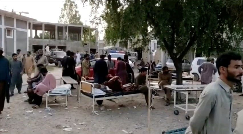 People gather outside a hospital following an earthquake in Harnai, Balochistan, Pakistan, October 7, 2021, in this still image obtained from video. (Reuters)