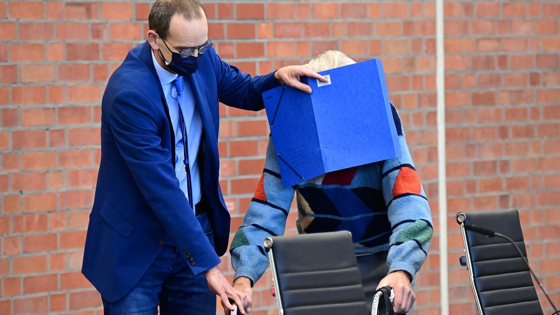 Defendant Josef S gets help from his lawyer Stefan Waterkamp (L) to hide his face behind a folder as he arrives for his trial in Brandenburg an der Havel, northeastern Germany, on October 7, 2021. (File photo: AFP)