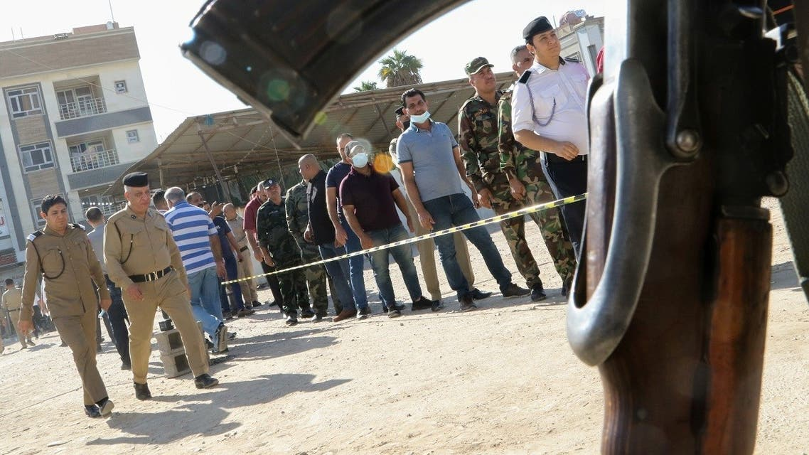 Members of Iraqi security forces line up outside a polling station waiting to cast their vote in a special process, two days ahead of Iraq's parliamentary elections, in Baghdad, Iraq October 8, 2021. (Reuters/Ahmed Saad)