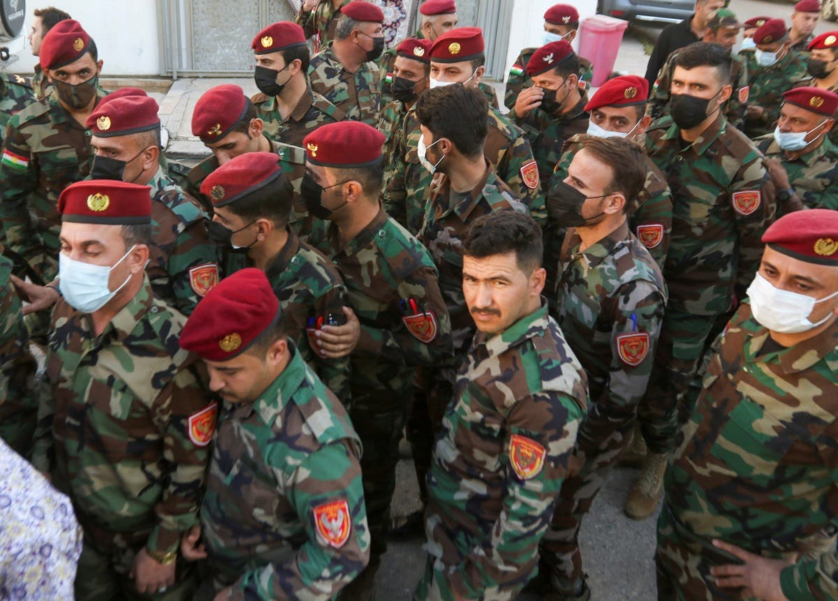 Members of Kurdish Peshmerga military forces line up inside a polling station, to cast their vote two days ahead of Iraq's parliamentary elections in a special process, in Erbil, Iraq October 8, 2021. (Reuters/Azad Lashkari)