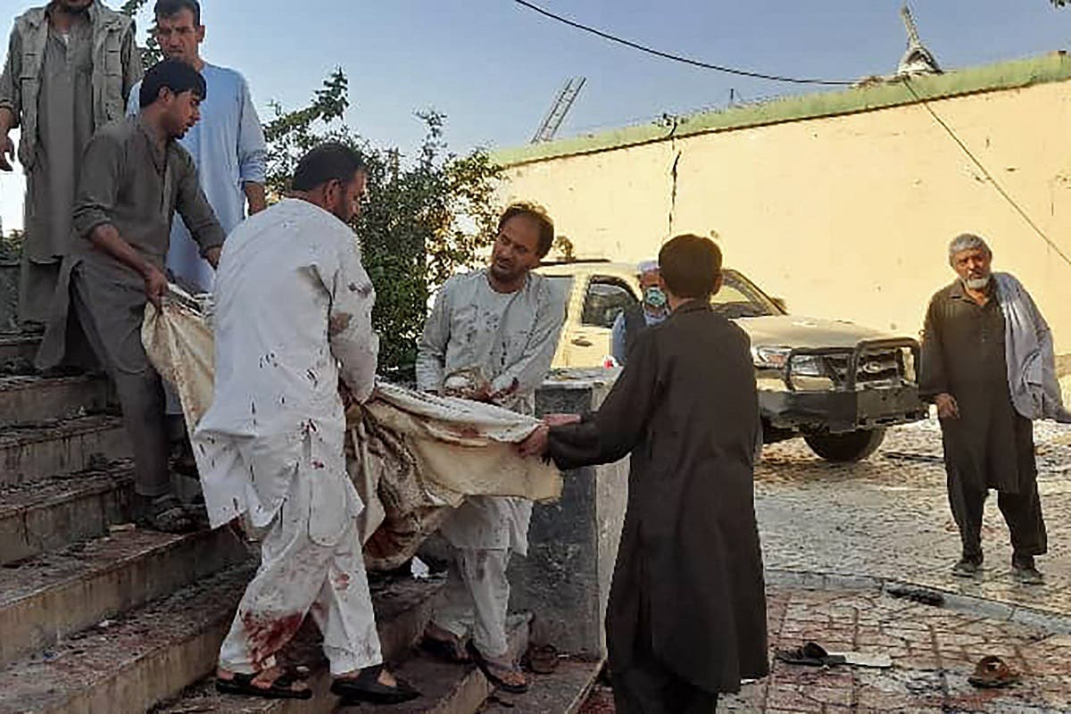 Afghan men carry the dead body of a victim to an ambulance after a bomb attack at a mosque in Kunduz on October 8, 2021. (AFP)