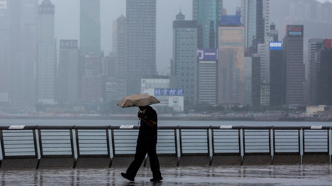 A man walks in the rain along Victoria Harbour in the Kowloon district of Hong Kong on August 16, 2021. (File photo; AFP)