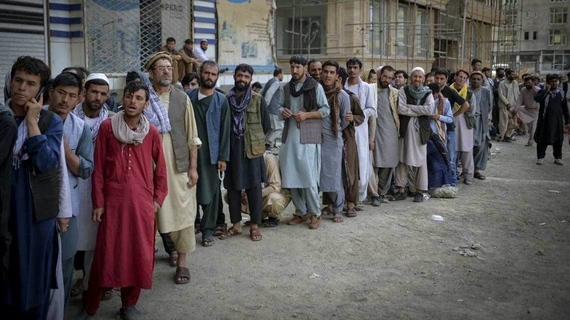 Afghans queue up as they wait for the banks to open and operate at a commercial area in Kabul on August 31, 2021. (AFP)