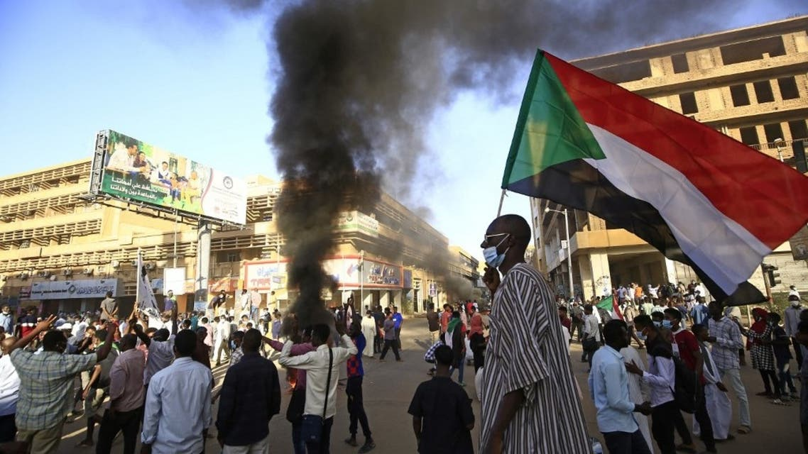 A Sudanese man wearing a face mask waves his country's national flag during protests in the capital Khartoum to mark the second anniversary of the start of a revolt that toppled the previous government, on December 19, 2020. (AFP)