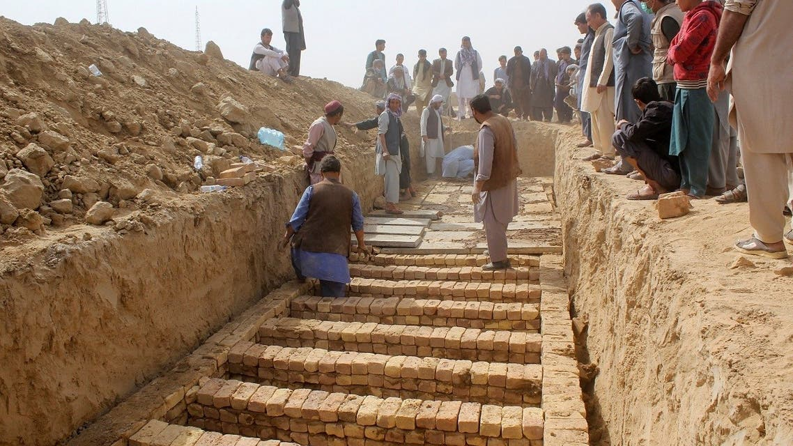 Afghan men dig graves during a mass funeral after the previous day's suicide bomb blast inside a mosque in Kunduz, Afghanistan October 9, 2021. (Reuters)