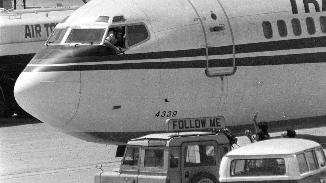 A Shiite Muslim hijacker points his pistol toward an ABC news media crew from the window of the cockpit of the Trans World Airlines jet at Beirut International Airport, June 19, 1985. (AP)