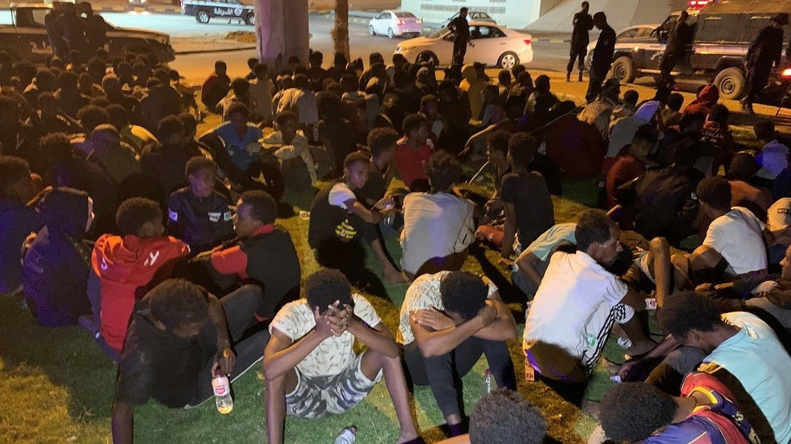 Migrants sit after they were detained by Libyan security forces in Tripoli, Libya, on October 8, 2021. (Reuters)